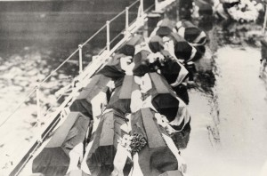 The coffins on board HMS Champion make their way to England