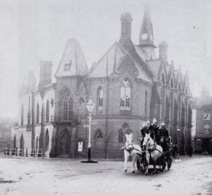 Firemen burst from the Town Hall to attend another fire, circa 1900.  They were relocated in 1969